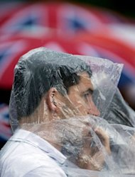 A spectator wears a plastic poncho as a shield from rain during the dressage event of the equestrian eventing competition at the London 2012 Olympic Games in Greenwich Park, London
