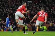 Manchester United&#39;s Dutch striker Robin van Persie (L) climbs on the back of Manchester United&#39;s Welsh midfielder Ryan Giggs (C) as Manchester United&#39;s English midfielder Tom Cleverley (R) runs in to celebrate Giggs&#39;s opening goal during the English Premier League football match between Manchester United and Everton at Old Trafford, Manchester, on February 10, 2013. United won 2-0