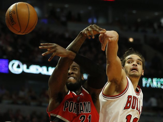 Portland Trail Blazers' J.J. Hickson and Chicago Bulls' Joakim Noah battle for a loose ball during the first half of their NBA basketball game in Chicago, Illinois