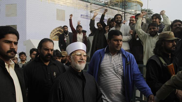 Pakistani cleric Tahir-ul-Qadri, center, surrounded by guards, is greeted by supporters after attending a press conference, in Lahore, Pakistan, Saturday, Jan. 12, 2013. After years in Canada, Qadri returned to Pakistan last month and gave a speech demanding that sweeping election reforms be implemented but it is his anti-government message that has drawn the most support in Pakistan. Many people are frustrated with a political system they believe is corrupt and dominated by two political parties: the Pakistan People's Party, which controls the government, and the opposition Pakistan Muslim League-Nawaz. Qadri plans to lead his followers in a march on the capital next Monday. (AP Photo/K.M. Chaudary)