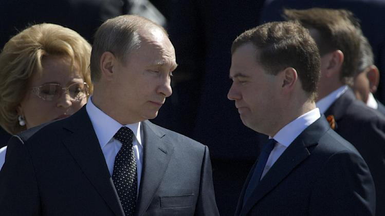 Russian President Vladimir Putin, left, and Prime Minister Dmitry Medvedev, right, attend a wreath laying ceremony at the Tomb of Unknown Soldier on the eve of Victory Day celebration in Moscow, Russia, Wednesday, May 8, 2013. Russia's marking the surrender of Nazi Germany in World War II on May 9th. (AP Photo/Ivan Sekretarev)