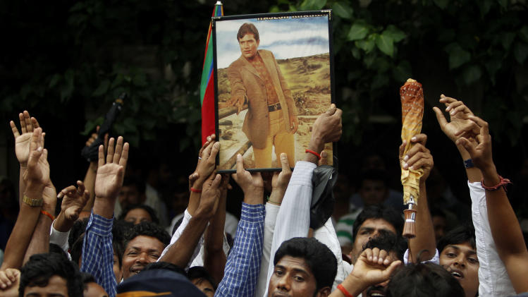 Fans hold a photograph of Bollywood superstar Rajesh Khanna during his funeral in Mumbai, India, Thursday, July 19, 2012. Khanna, whose success as a romantic lead in scores of Indian movies made him Bollywood's first superstar, died Wednesday after a brief illness. He was 69. (AP Photo/Rafiq Maqbool)