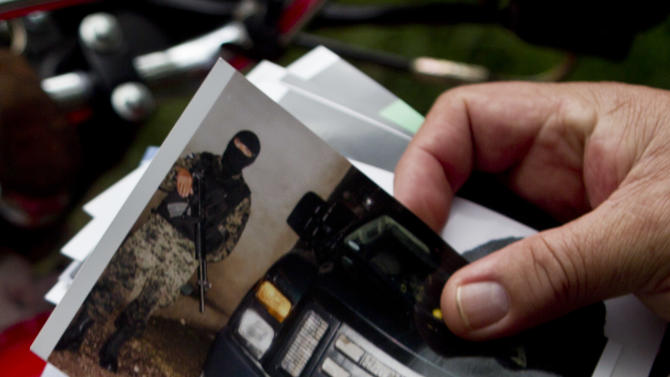 In this photo taken on Wednesday, Oct 17, 2012, Wilfredo Yanez shows photos of a masked soldier at a military checkpoint near which his son Abed Jaasiel Yanez was allegedly shot dead in Tegucigalpa, Honduras. According to his relatives, Jaasiel was killed by soldiers early Sunday, May 27, when he was riding a motorcycle, near a military checkpoint, allegedly accompanied by a young woman.  (AP Photo/Esteban Felix)