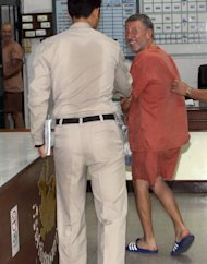 Vito Roberto Palazzolo, left, a fugitive Italian banker, is escorted to a court cell as he arrives for an extradition trial at criminal court in Bangkok, Thailand, Thursday, Dec, 20, 2012. Palazzolo, 64, who was implicated in the drug and money laundering trial, was detained at Suvarnabhumi international airport in Bangkok on March 30 while about to board a flight to South Africa. He is wanted in Italy where he faces a nine-year prison sentence for links with the Mafia. (AP Photo/Apichart Weerawong)