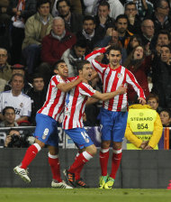 Atletico de Madrid's Adrian Lopez, right, celebrates his goal with Eduardo Salvio of Argentina, left, and Gabi, center, during the Spanish La Liga soccer match against Real Madrid at the Santiago Bernabeu stadium, in Madrid, Spain, Saturday, Nov. 26, 2011. (AP Photo/Andres Kudacki)