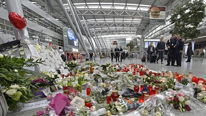 Passengers watch candles and flowers for the victims of the plane crash at the airport in Dusseldorf , Germany, Tuesday, March 31, 2015. One week ago 150 people died in the Germanwings airliner crash in the French alps from Barcelona to Duesseldorf. (AP Photo/Martin Meissner)