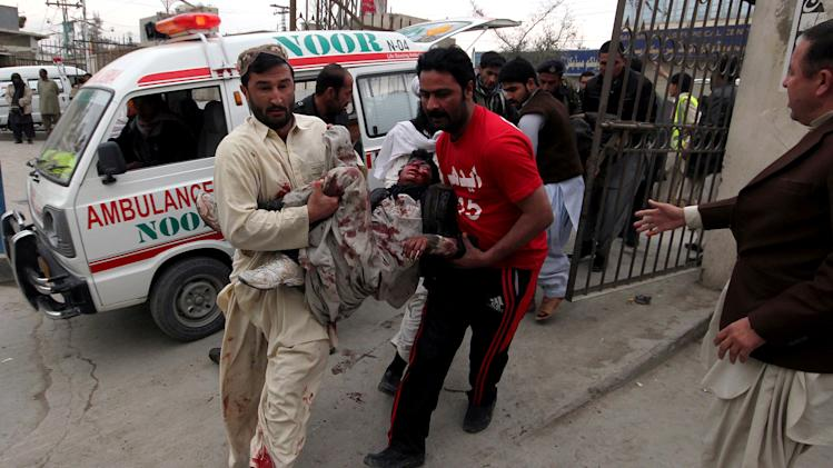 Pakistani volunteers rush an injured victim from a bomb blast to a local hospital for treatment in Quetta, Pakistan, Thursday, Jan. 10, 2013. A bomb targeting paramilitary soldiers killed scores of people in southwest Pakistan, officials said. (AP Photo/Arshad Butt)