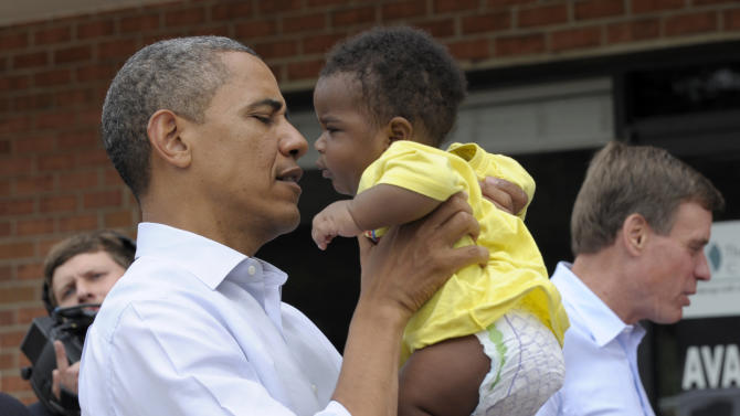 President Barack Obama picks up Kerry Christophe III during a stop at Rick's Cafe in Virginia Beach, Va., Friday, July 13, 2012. Obama is spending the day in Virginia campaigning. Sen. Mark Warner, D-Va., is at right.  (AP Photo/Susan Walsh)