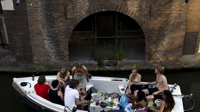 """People have a meal on a boat as they sail along the Oudegracht, or """"old canal"""", in downtown Utrecht"""