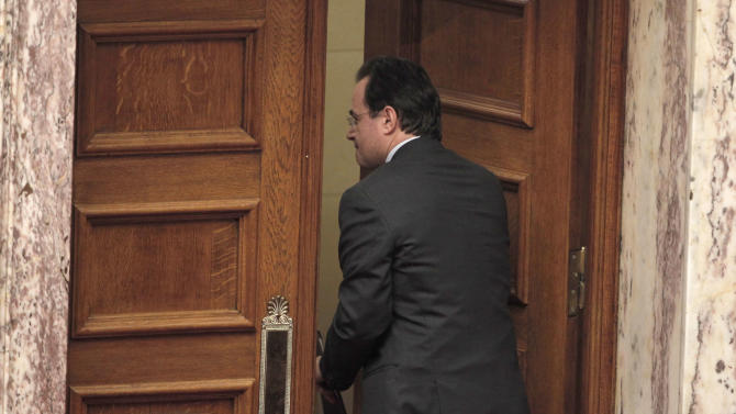 Former finance minister Georges Papakonstantinou leaves the main session hall of the Parliament after addressing to its members in Athens on Thursday Jan. 17, 2013.  Greece's Parliament is debating whether to investigate four former senior members of the government including Papaconstantinou, over how leaked data on Greeks who banked in Switzerland was handled. All four deny wrongdoing.  (AP Photo/Petros Giannakouris)