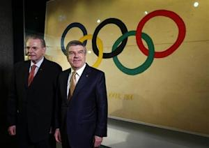IOC President Bach poses with his predecessor Rogge in a new presentation room at the Olympic Museum in Lausanne