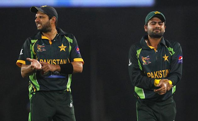 Pakistan's Shahid Afridi, left, points towards his wrist to indicate an injury on teammate Ahmed Shehzad during the Asia Cup final cricket match between Sri Lanka and Pakistan in Dhaka, Bangladesh, Sa