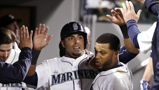 Seattle Mariners' Nelson Cruz is congratulated in the dugout after scoring against the Houston Astros in the fifth inning of a baseball game Monday, April 20, 2015, in Seattle. (AP Photo/Elaine Thompson)