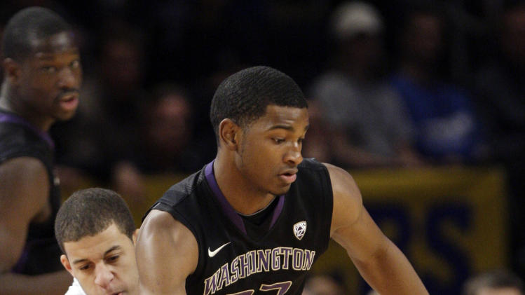 Washington's C.J. Wilcox (23) protects the ball from Duke's Seth Curry, left, during the first half of an NCAA basketball game during the CARQUEST auto parts classic, Saturday, Dec. 10, 2011, in New York. (AP Photo/Frank Franklin II).