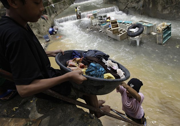 Residents clean their clothes along a river as floods recede in suburban Marikina city, east of Manila, Philippines, Friday Aug. 10, 2012. Philippine disaster officials were shifting Friday from rescu