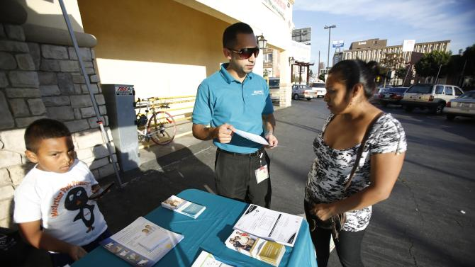 Corona, patient care coordinator at AltaMed, speaks to a woman during a community outreach on Obamacare in Los Angeles