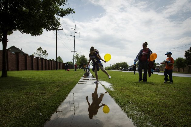Plaza Towers elementary school student Kayla Billy leans over a puddle in front of her mother Jennifer Billy and brother Ethan Billy as she departs a ceremonial last day of the school year for student