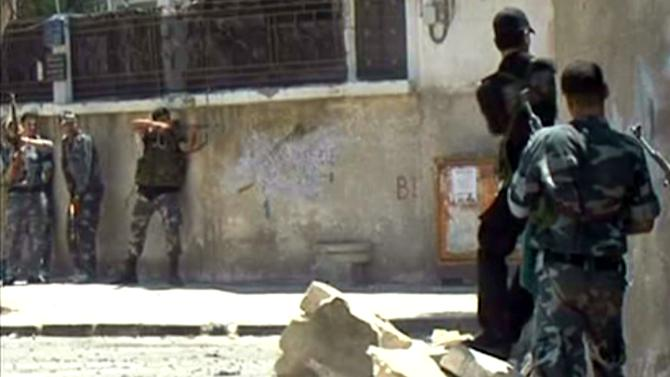 This image made from video released by the Syrian official news agency SANA purports to show Syrian troops fighting against the Syrian rebels, in the Al-Midan area, in Damascus, Syria, Tuesday July 18, 2012. A bomb ripped through a high-level security meeting Wednesday in Damascus, killing three top regime officials ? including President Bashar Assad's brother-in-law in the harshest blow to Syria's ruling family dynasty and the rebels' boldest attack in the country's civil war. (AP Photo/SANA)
