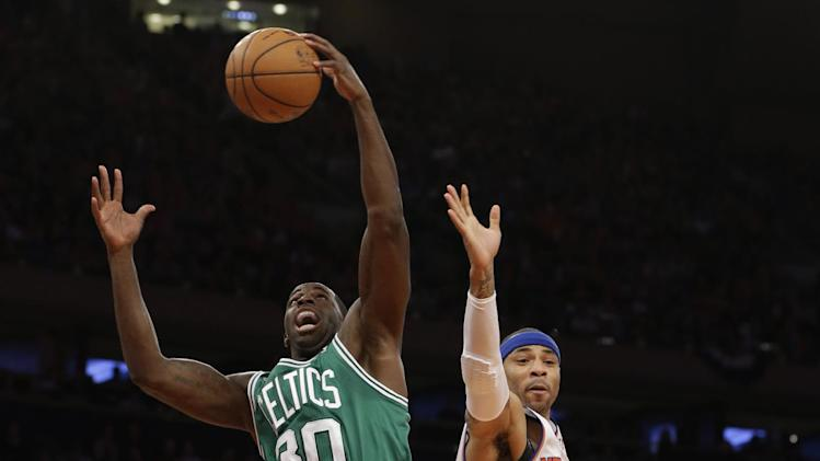 Boston Celtics forward Brandon Bass (30) grabs the ball in front of New York Knicks forward Kenyon Martin (3) during the first half of Game 1 in the first round of the NBA basketball playoffs at Madison Square Garden in New York, Saturday, April 20, 2013.  (AP Photo/Kathy Willens)
