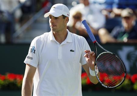 John Isner of the U.S. spins his racket after getting aced on a serve from Lleyton Hewitt of Australia during their match at the BNP Paribas Open ATP tennis tournament in Indian Wells
