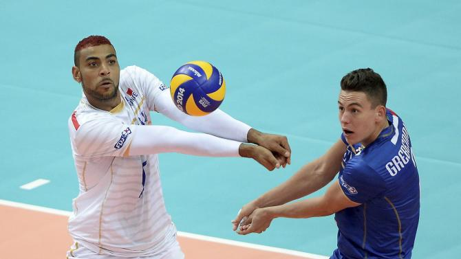 France's Ngapeth hits a ball next to his teammate Grebennikov during their third round match against Iran at the FIVB Volleyball Men's World Championship Poland 2014 at the Katowicki Spodek in Katowice