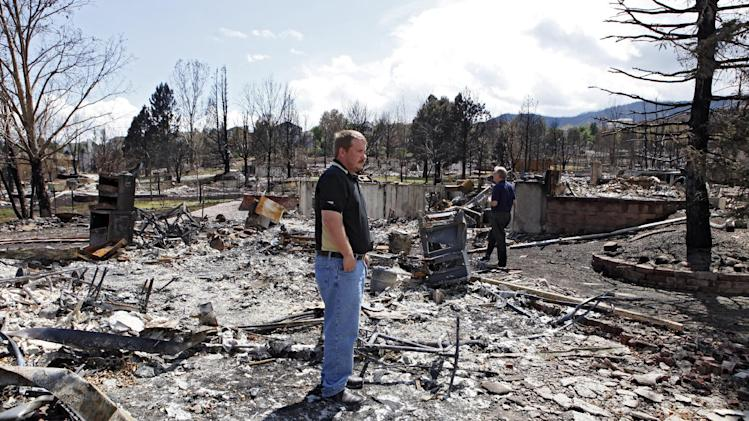 Members of FEMA and the Small Business administration look at a burned home in Colorado Springs, Colo., on Monday, July 9, 2012. Members of FEMA, the SBA and Colorado's Disaster Office assessed damages in the area burned by the Waldo Canyon wildfire.  (AP Photo/Ed Andrieski)