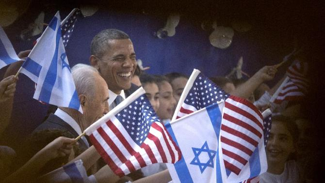 President Barack Obama and Israeli President Shimon Peres, left, are photographed through a window and the crowd as they are greeted by children waving Israeli and American flags upon their arrival at the Peres' residence, Wednesday, March 20, 2013, in Jerusalem. (AP Photo/Carolyn Kaster)