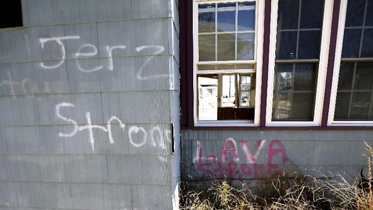 In this photograph taken Friday, Oct. 18, 2013, shows writing on the outside of the vacation home of Cora Hoch in Lavallette, N.J. The home, which was damaged by Superstorm Sandy, has been gutted and no repair has been made to it while neighbor homes are up and running again. Billions of dollars in federal rebuilding and aid and insurance payments have helped many full-time Jersey shore residents to recover. But many property owners of modest means who had scrimped and saved to buy vacation homes on the shore, or may have inherited their getaway bungalows and cottages, have struggled to pull together enough money to hang on and rebuild. (AP Photo/Julio Cortez)