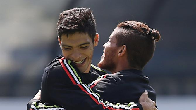 Mexico's soccer player Jimenez hugs teammate Santos during a soccer training session in Mexico City