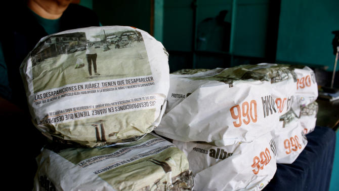 One kilogram packages of corn tortillas, packaged with advertisements asking for help to find missing women and children, sit for sale at the Hermanos Escobar Tortilla shop in the northern border city of Ciudad Juarez, Mexico, Tuesday Nov. 13, 2012.  At least three dozen tortilla shops have joined in the Chihuahua state campaign to print appeals for help on the thin paper wrappers that shopkeepers use to wrap up a pound or two of hot tortillas at a time. (AP Photo/Raymundo Ruiz)