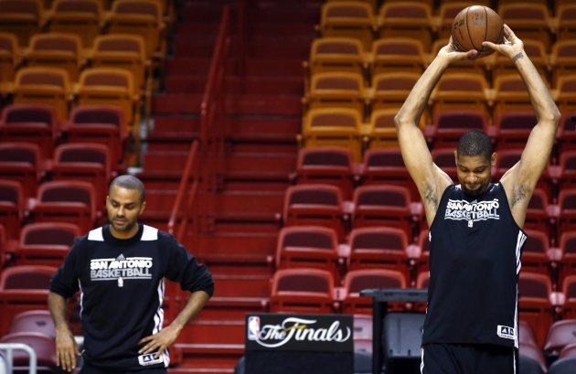 San Antonio Spurs' Duncan and Parker stretch during a team practice ahead of Game 7 of the NBA Finals basketball playoff against the Miami Heat in Miami