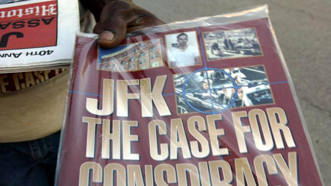 "FILE - In this Saturday, Nov. 8, 2003 file photo, a vendor holds up a magazine-style publication titled ""JFK The Case For Conspiracy"" in downtown Dallas. (AP Photo/Donna McWilliam)"