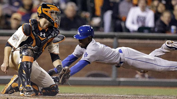 Los Angeles Dodgers' Dee Gordon, right, dives to score behind San Francisco Giants catcher Buster Posey in the seventh inning of a baseball game Saturday, May 4, 2013, in San Francisco. Gordon scored on a single by Dodgers' Carl Crawford. (AP Photo/Ben Margot)