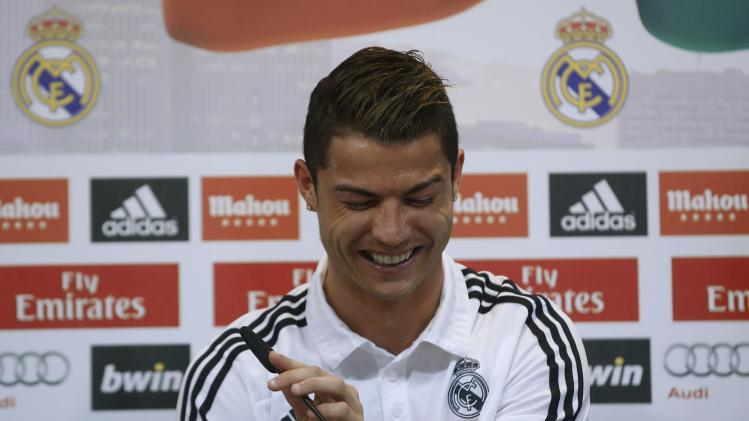Real Madrid's Cristiano Ronaldo reacts as he attends a news conference to discuss the draw for the 2014 World Cup at the Valdebebas training grounds, outside Madrid