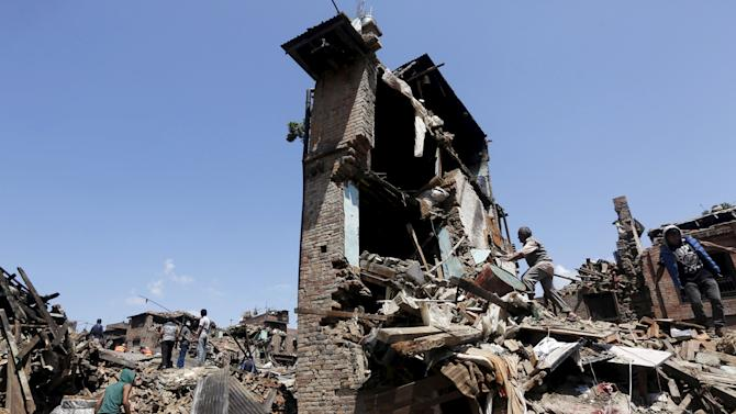 Man looks into his damaged house to recover belongings following Saturday's earthquake in Bhaktapur, Nepal