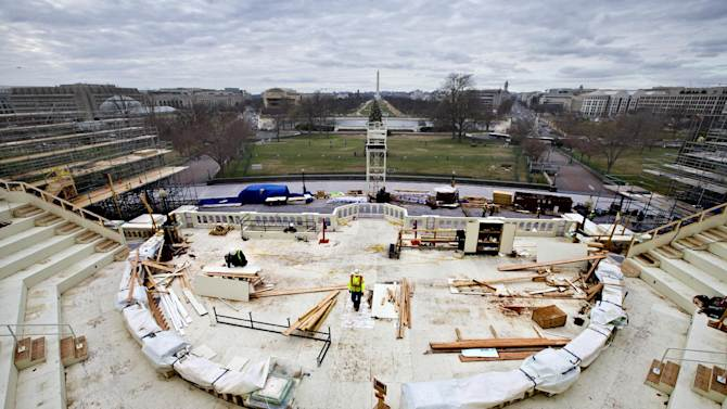 With forty days until President Barack Obama is sworn in for a second term, construction workers continue work on the platforms on the west side of the Capitol where dignitaries and news cameras will witness the inaugural ceremonies, looking toward the Washington Monument, Tuesday, Dec. 11, 2012, on Capitol Hill in Washington.   (AP Photo/J. Scott Applewhite)