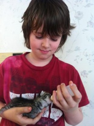 Maxwell feeds his kitten, Steve, with a bottle. Steve, who is female, is named after a Minecraft character.