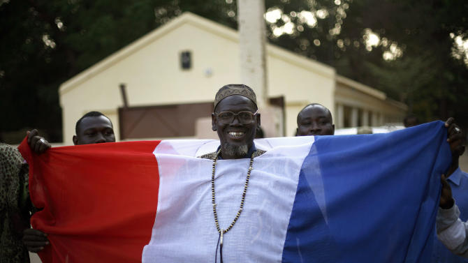 A Malian well-wisher displays his French flag as French soldiers enter Niono, Mali, some 400 kms (300 miles) north of the capital Bamako Saturday Jan. 19, 2013. French troops encircled a key Malian town on Friday, trying to stop radical Islamists from striking against communities closer to the capital and cutting off their supply line, a French official said.  The move around Diabaly came as French and Malian authorities said that the city whose capture prompted the French military intervention in the first place was no longer in the hands of the extremists.(AP Photo/Jerome Delay)