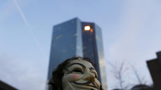 A Blockupy protester with a mask of Guy Hawkes on the back of his head walks at the end of a demonstration against the opening of the new European Central Bank (ECB) headquarters in Frankfurt
