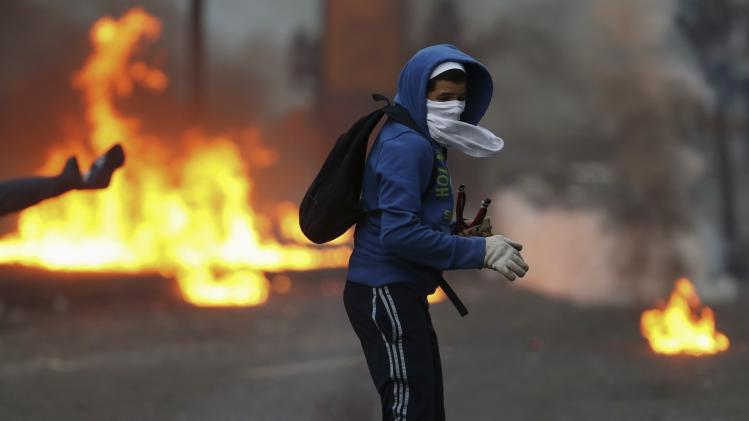 An anti-government protester turns after throwing a molotov at police during clashes in Caracas
