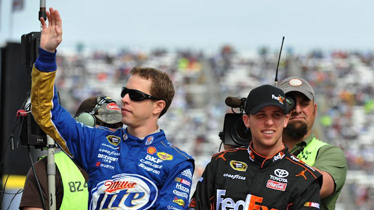 NASCAR race car drivers Brad Keselowski, left, and Denny Hamlin are seen  during driver introduction ceremonies before NASCAR's Sprint Cup Series auto race at Martinsville Speedway, Sunday, Oct. 28, 2012, in Martinsville, Va. (AP Photo/Don Petersen)