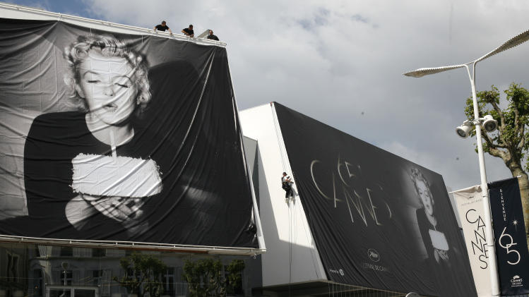 Workers set up giants 65th Cannes Film Festival official posters showing Marilyn Monroe on the Cannes Festival Palace, Monday, May 14, 2012. The Cannes Film Festival will start on Wednesday, May 16.(AP Photo/Lionel Cironneau)