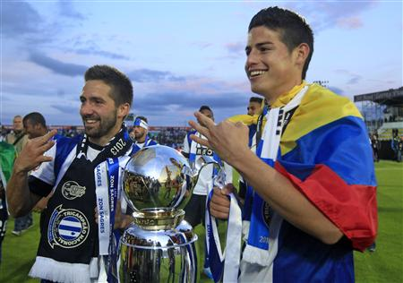 Porto's Moutinho and team mate Rodriguez hold the trophy while they celebrate winning the Portuguese Premier League title after their soccer match against Pacos Ferreira at the Mata Real stadium in Pa