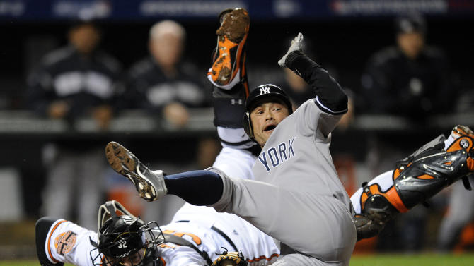 New York Yankees' Ichiro Suzuki, right, of Japan, leaps past Baltimore Orioles catcher Matt Wieters to score a run on a double by Robinson Cano in the first inning of Game 2 of the American League division baseball series on Monday, Oct. 8, 2012, in Baltimore. (AP Photo/Nick Wass)