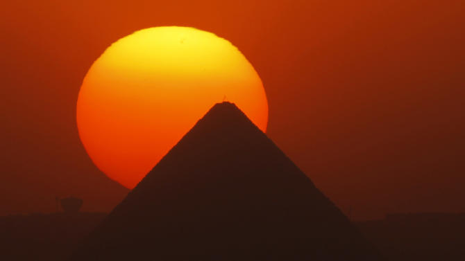 The sun sets behind the Great Pyramid in Giza, Egypt