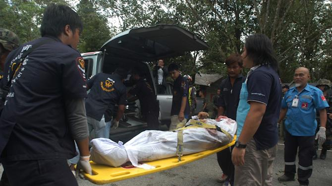 Thai volunteer rescue workers unload one of dead bodies of insurgents upon arrival in Narathiwat province Wednesday, Feb. 13, 2013. Thai soldiers fending off a major assault on a military base in the country's violence-plagued south killed 19 insurgents, authorities said Wednesday. The death toll was believed to be the biggest inflicted on the Muslim guerrillas since more than 100 died in a single day nearly a decade ago. (AP Photo/Sumeth Panpetch)