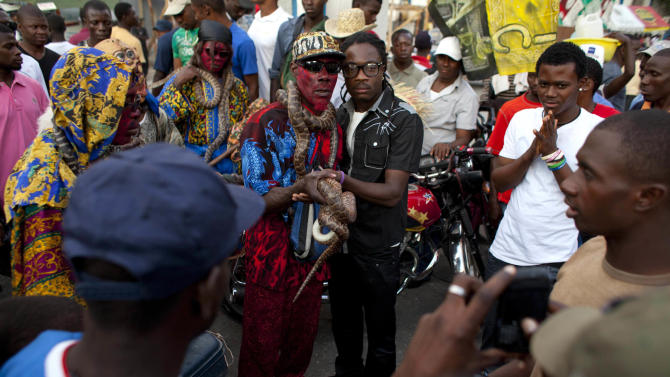 In this Jan. 27, 2013 photo, snake handler Saintilus Resilus, center left, holds his snake as he poses for photos with a spectator as he performs for money during pre-Lenten Carnival season in Petionville, Haiti. Resilus has used snakes and other animals to earn a little money since at least 1974. (AP Photo/Dieu Nalio Chery)