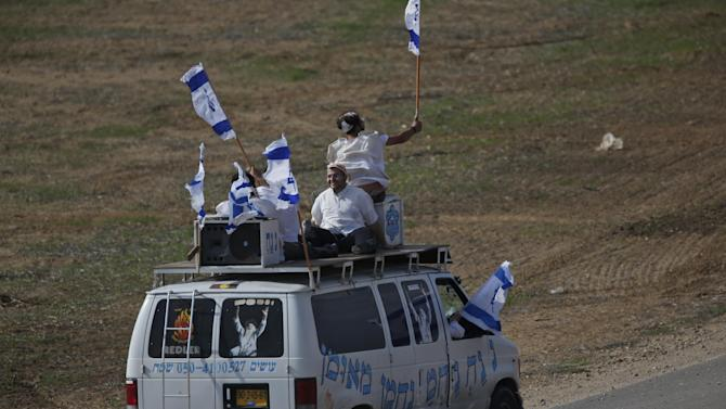 Ultra-Orthodox Jews of the Bratslav Hasidic sect, in support of the Israeli forces, hold national flags on top of a van with the name of their spiritual leader Rabbi Nachman of Uman, right, as they drive towards the border with the central Gaza Strip, Monday, Nov. 19, 2012. Israeli aircraft struck crowded areas in the Gaza Strip and killed a senior militant with a missile strike on a media center Monday, driving up the Palestinian death toll to 96, as Israel broadened its targets in the 6-day-old offensive meant to quell Hamas rocket fire on Israel. (AP Photo/Lefteris Pitarakis)