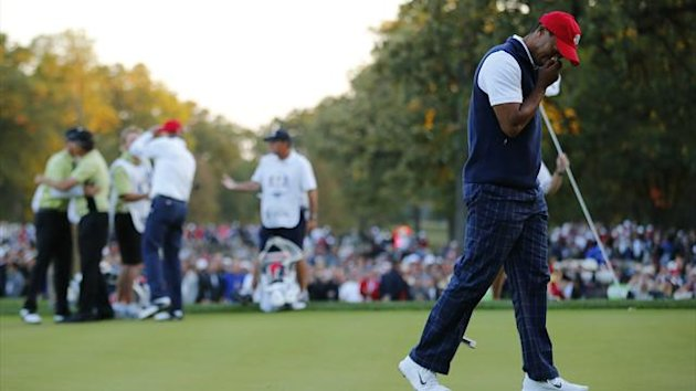 Tiger Woods reacts to missing a birdie putt and losing the match as Team Europe golfers Lee Westwood and Nicolas Colsaerts (L) celebrate on the 18th green during the afternoon four-ball round at the 39th Ryder Cup golf matches at Medinah (Reuters)