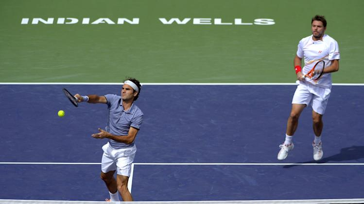 Roger Federer returns a volley as he and doubles partner Stanislas Wawrinka, both of Switzerland, play Rohan Bopanna, of India, and Aisam-Ul-Haq Qureshi, of Pakistan, at the BNP Paribas Open tennis tournament Friday, March 7, 2014, in Indian Wells, Calif. (AP Photo/Mark J. Terrill)
